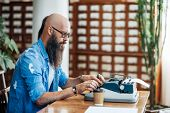 Bearded Stylish Writer Typing On Typewriter. Modern Writer In Glasses Working On New Book In Library poster