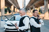 Mature Police Officer Talking On Smartphone And Standing With Colleague Back To Back While He Writin poster