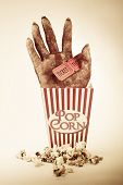 stock photo of gruesome  - Frightening Picture Of A Creepy Sawn Off Hand Poking Out Of A Striped Pop Corn Box Holding Two Cinema Movie Tickets In A Horror Movie Conceptual - JPG