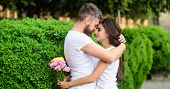Couple In Love Hugs On Date In Park Green Bushes Background. Man Fall In Love With Gorgeous Girl. Ma poster