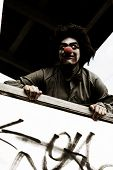 foto of unnerving  - Creepy Clown Standing On A Verandah With A Scary Smile During A Halloween Trick Or Treat Session - JPG