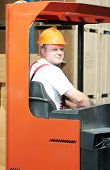 young worker men in uniform at warehouse with forklift stacker facilities