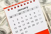 stock photo of overspending  - Calendar and dollar January New Year for background use - JPG