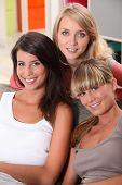 Three female housemates relaxing on sofa
