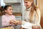 stock photo of polite girl  - Little girl giving her mother a crepe - JPG