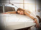 Dream About Car. Gorgeous Smiling Woman Hugging Lies On The Hood Of New White Car In The Dealership. poster