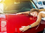 Dream About Car. Gorgeous Smiling Woman Hugging Lies On The Hood Of New Red Car In The Dealership. poster