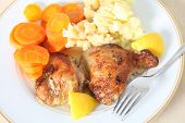 picture of thigh highs  - A high angle view of chicken thighs marinaded in lemon juice and herbs and then roasted served with mashed boiled potatoes and boiled carrots - JPG