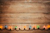 Vintage Christmas Lights Bulb Decoration On Old Wood Plank. Merry Christmas And New Year Holiday Bac poster