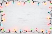 Christmas Lights Bulb Frame Decoration On White Wood. Merry Christmas And New Year Holiday Backgroun poster