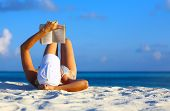 picture of girl reading book  - Young women is resting on the coral beach Maldives - JPG