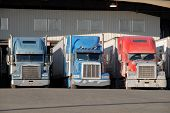 stock photo of loading dock  - three semi trucks at warehouse waiting to be loaded - JPG