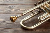 Aged Trumpet On Wooden Background. Old Trumpet With Brassy Mouthpiece. Classical Music Instrument. poster