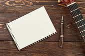 Blank Notebook, Pen And Guitar. Brown Wooden Background With Blank Paper Copy Book, Guitar And Pen.  poster
