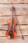 Violin And Fiddle Stick On Wooden Planks. Vintage Violin And Bow On Old Wooden Boards, Top View. poster