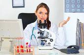 Confundida mujer médico que trabaja con microscopio en el laboratorio