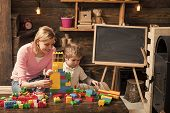 Mother And Happy Son Play With Constructor. Motherhood Concept. Nursery With Toys And Chalkboard On  poster