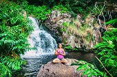 Yoga retreat woman praying doing the lotus pose meditating at waterfall forest in Kauai, Hawaii. Spi poster