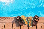 Two pairs (men's and woman's) of flip-flops by sunny swimming pool