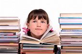 Portrait of cute girl sitting among stacks of books isolated on white background