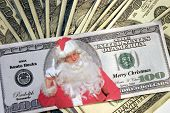 Santa Bucks (Featuring Yours Truly as Santa Himself) lays across a pile of cash