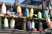 various ocean bouys of diffrent colors and sizes hang from a deck on the beach