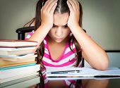 image of boredom  - Angry and tired schoolgirl studying with a pile of books on her desk - JPG