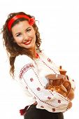 Beautiful ukrainian young woman in native costume holding earthenware pots over white background