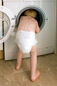 Young Child Climbing Inside A Washing Machine