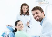 Dentist, his assistant and the patient are preparing to treat carious teeth
