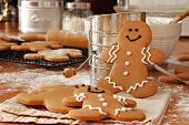 Smiling gingerbread man standing next to flour sifter with baking ingredients and additional gingerb