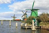The village - an ethnographic museum in Holland. Three windmills and berthing columns on the bank of