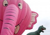 READINGTON, NJ-JUL 29: A close up of the Nelly B Pink Elephant and T-Rex balloons tethered to the gr