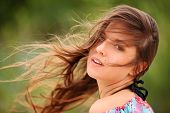 stock photo of windswept  - Portrait of  young woman smiling with windswept hair - JPG