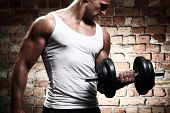 stock photo of barbell  - Muscular guy doing exercises with dumbbell against a brick wall - JPG