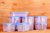 foto of tupperware  - Plastic containers for food on wooden background - JPG