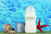 deodorant, fishstar and shells on blue sea background