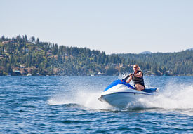 foto of waverunner  - Beautiful woman out on the lake riding a wave runner on bright sunny day - JPG