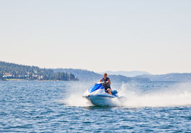 stock photo of waverunner  - Beautiful woman out on the lake riding a wave runner on bright sunny day - JPG