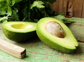 stock photo of avocado  - ripe avocado cut in half on a wooden table - JPG