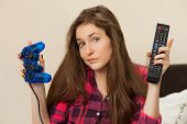 Young woman can't choose between TV console and joystick