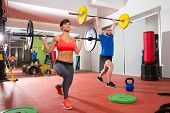 stock photo of heavy equipment  - Crossfit fitness gym weight lifting bar by woman and man group workout - JPG