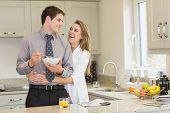 Woman hugging her husband while eating cereal in kitchen