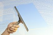 picture of soapy  - Closeup of a hand cleaning windows with a squeegee - JPG