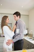 Woman fixing tie of husband before work in kitchen