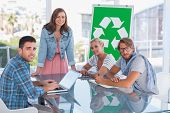 pic of take responsibility  - Team having meeting about recycling and smiling at camera in bright office - JPG