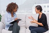 Umwerfen weiblich zu ihrem Therapeuten zu sprechen, während sie Notizen ist