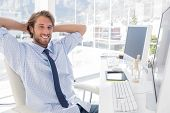 Smiling designer at his desk in bright modern office