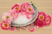 Rose flower spa arrangement with sea salt in an abalone shell and sponge over bamboo background. Carefree days variety.