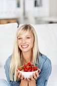 foto of strawberry blonde  - Smiling attractive young blonde woman with a bowl of delicious ripe red strawberries held in her hands - JPG